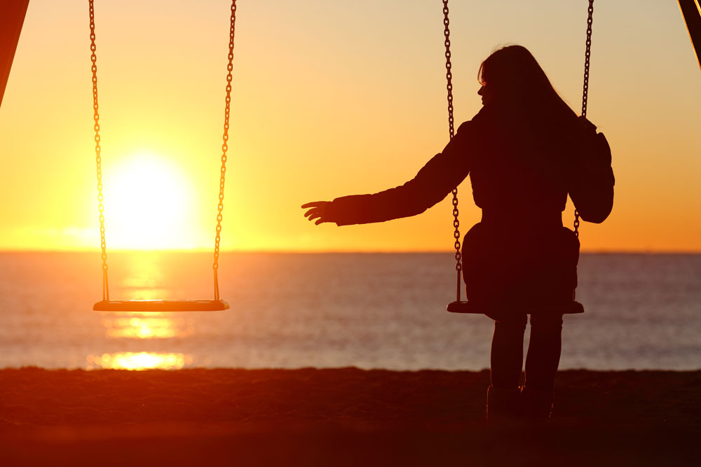 Image of a woman sitting on a swing, reaching out to the swing beside her, which is empty.